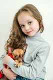 Blond kid girl with small pet dog Royalty Free Stock Photos