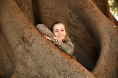 Blond kid girl smiling arms on big Ficus tree stock image