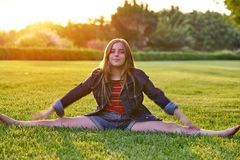 Blond kid girl splitting legs at sunset park Royalty Free Stock Images
