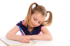 Blond kid girl student with spiral notebook in desk. Blond kid indented girl student with spiral notebook in pupil desk stock photo