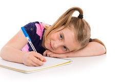 Blond kid girl student with spiral notebook in desk Stock Photos