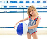 Blond kid girl with swimsuit with summer blue ball. In balconade royalty free stock photos