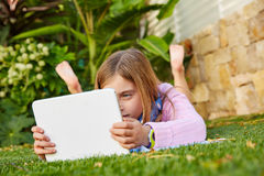 Blond kid girl with tablet pc lying on grass turf Royalty Free Stock Photo