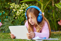 Blond kid girl with tablet pc lying on grass turf Royalty Free Stock Images