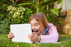 Blond kid girl with tablet pc lying on grass turf Royalty Free Stock Photos