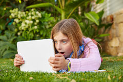 Blond kid girl with tablet pc lying on grass turf Stock Photos
