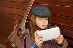 Blond kid girl taking selfie guitar and winter beret Royalty Free Stock Images