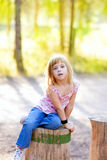 Blond kid girl in tree trunk forest Royalty Free Stock Photo