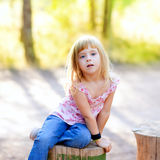 Blond kid girl in tree trunk forest Stock Image