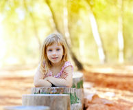 Blond kid girl in tree trunk forest Royalty Free Stock Photography