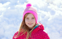 Blond kid girl winter hat in the snow smiling Stock Photo