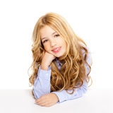 Blond kid little girl smiling on a desk in white Royalty Free Stock Photos