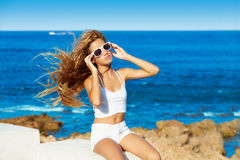 Blond kid teen girl on the beach long curly hair Stock Photos