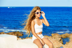 Blond kid teen girl on the beach long curly hair Royalty Free Stock Photos