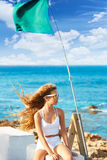 Blond kid teen girl on the beach long curly wind hair. Blond kid teen girl on the beach long curly hair at wind and green flag Royalty Free Stock Image
