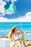 Blond kid teen girl on the beach long curly wind hair. Blond kid teen girl on the beach long curly hair at wind and green flag Stock Photo