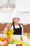 Blond kind girl junior chef on countertop Royalty Free Stock Photography