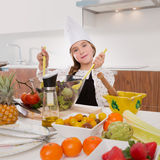 Blond kind girl junior chef on countertop salad Stock Photos