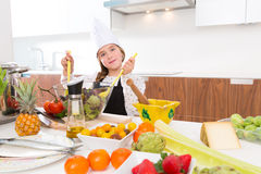 Blond kind girl junior chef on countertop salad Stock Photography