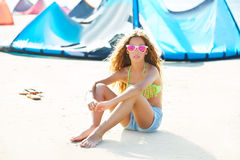 Blond kite surf teen girl in summer beach sitting. On sand Royalty Free Stock Images