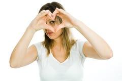 Blond kobieta pokazuje kierowego kształt z rękami symbol miłość - patrzejący przez serca - zdjęcie royalty free
