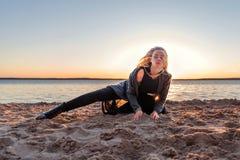 Blond kobieta spadał na piaska tanu na plaży podczas zmierzchu fotografia royalty free