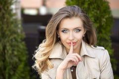 Blond kobieta stawiał forefinger wargi jak znaka cisza obraz royalty free