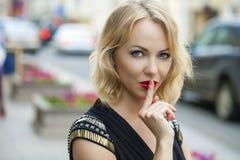 Blond kobieta stawiał forefinger wargi jak znaka cisza zdjęcia stock