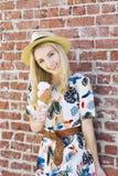 Blond kobieta stojaki Przeciw ścianie z cegieł Z lody rożkiem Jest ubranym Fedora Outdoors w lecie zdjęcia stock