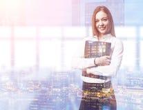Blond kobieta trzyma czarną falcówkę w jej biurze Zdjęcia Stock