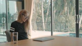 Blond kobieta typy w komputer zamykają je i rozciągają przy jej stołem w domu Freelance poj?cie zdjęcie wideo