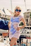 Blond kobieta w białej przejrzystej sukni i swimsuit pozyci na jachcie Zdjęcie Stock