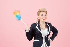 Blond kobieta w biuro mundurze z barwionym duster w ręki i twarzy wyrażeniu Dziewczyna w kurtce z duster w rękach na menchiach zdjęcia royalty free