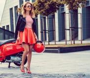 Blond kobieta w czerwieni spódnicowy iść zdala od czerwonej moto hulajnoga Obraz Royalty Free