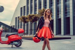 Blond kobieta w czerwieni spódnicowy iść zdala od czerwonej moto hulajnoga Obrazy Stock
