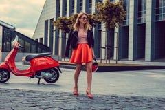 Blond kobieta w czerwieni spódnicowy iść zdala od czerwonej moto hulajnoga Fotografia Stock