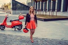 Blond kobieta w czerwieni spódnicowy iść zdala od czerwonej moto hulajnoga Zdjęcie Royalty Free