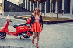 Blond kobieta w czerwieni spódnicowy iść zdala od czerwonej moto hulajnoga Zdjęcia Royalty Free