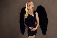 Blond kobieta z czarnymi aniołów skrzydłami Obraz Royalty Free