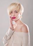 Blond kobieta z krótkim włosy dotyka wargi zdjęcie stock