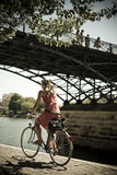 Blond kobieta z rowerem pod mostem sztuki w Paryż Zdjęcie Royalty Free