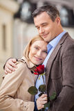 Blond kobiety mienia czerwieni róża i ono uśmiecha się przy kamerą Zdjęcia Stock
