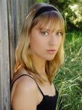 Blond kobiety obsiadanie Przeciw ogrodzeniu W Zielonej trawie obraz royalty free