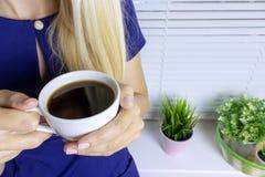Blond kobiety pozycja blisko okno zamykającego z bielem ślepi kawę i pije zdjęcie royalty free