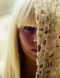 Blond kobiety twarz za siecią obraz stock