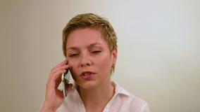 Blond krótkiego włosy blond dziewczyna opowiada telefonem komórkowym zbiory wideo