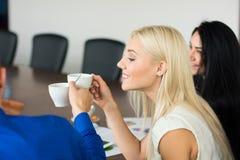 Blond kvinna för affär med en kopp kaffe med framstickandet i Arkivfoton