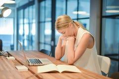 Blond kvinna för deprimerad affär som har problem med hennes arbeten Arkivbild