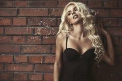 Blond kvinna för mode över tegelstenväggen Royaltyfria Foton