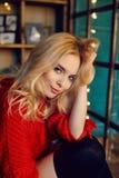 Blond kvinna för sexigt mode i det röda tröjasammanträdet på sängen och leendena Hemmastadd glödande girland Stående av en flicka Royaltyfri Foto